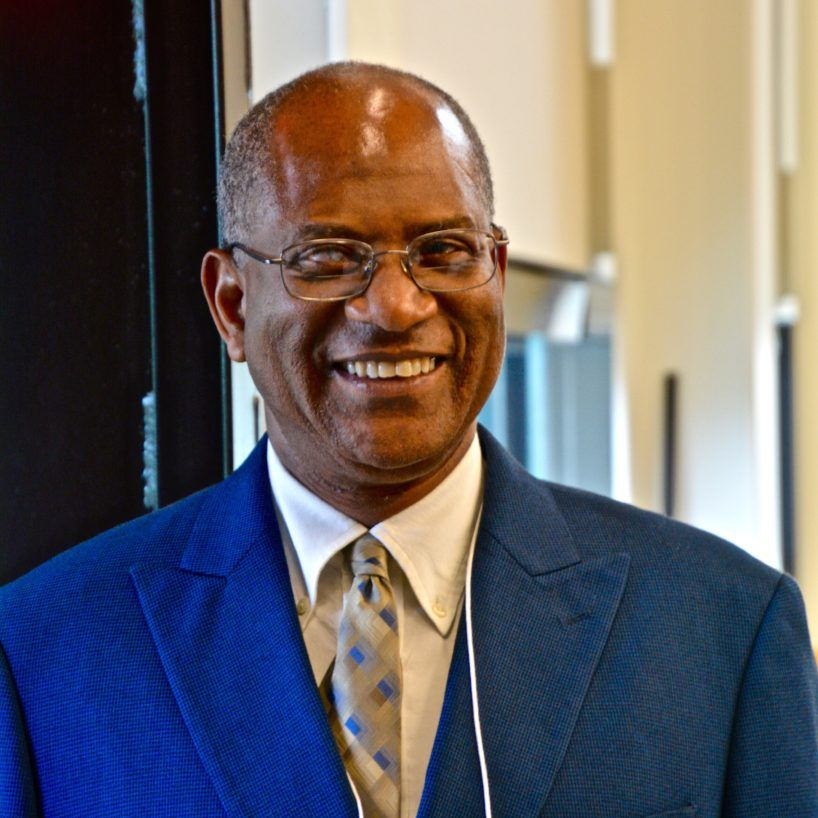 black man wearing blue suit and tie, smiling, wearing glasses
