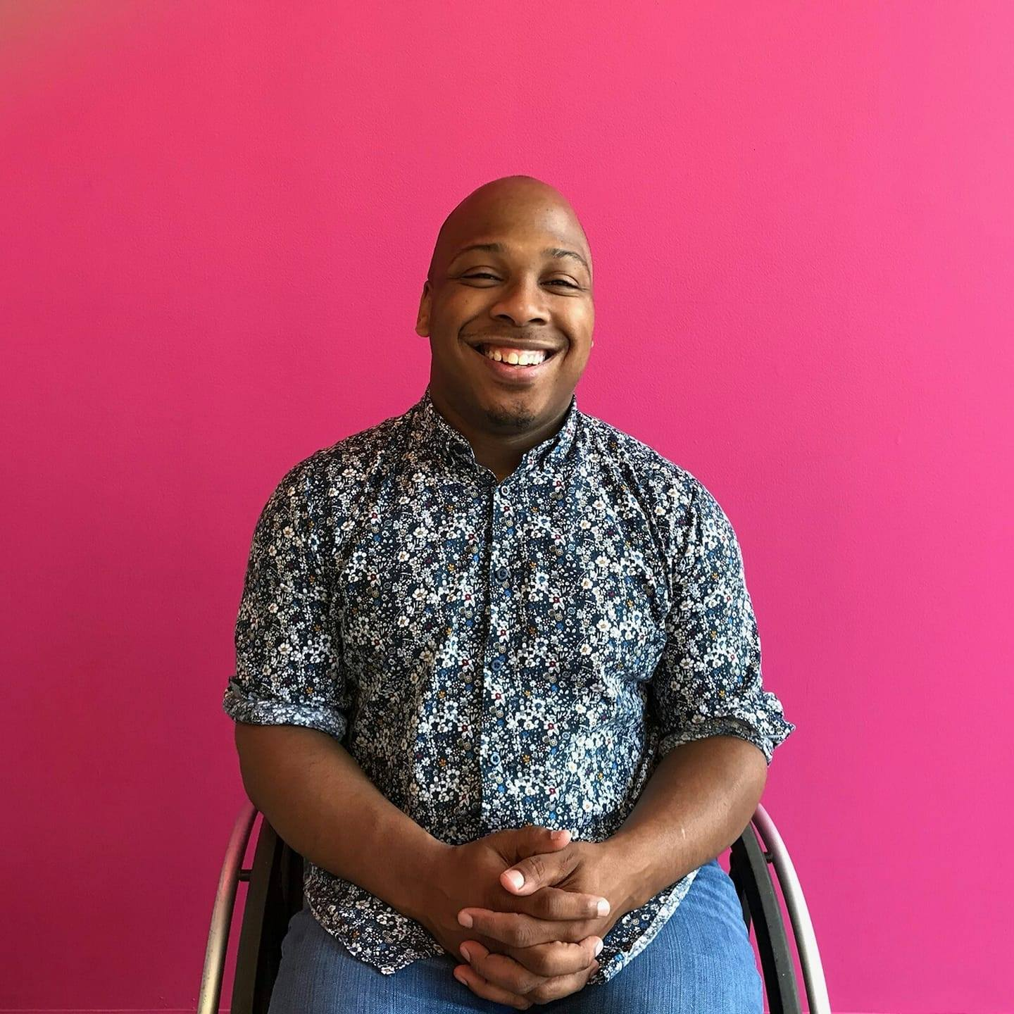 Patrick, a young black man, sits in wheelchair, hands folded, bright pink background