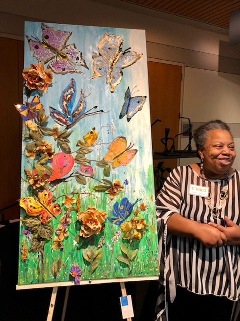 Angela standing next to her painting on an easel. Painting is large 3 dimensional collage of butterflies and flowers.