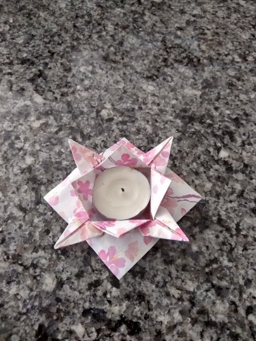 origami of a decorative container holding a votive candle.