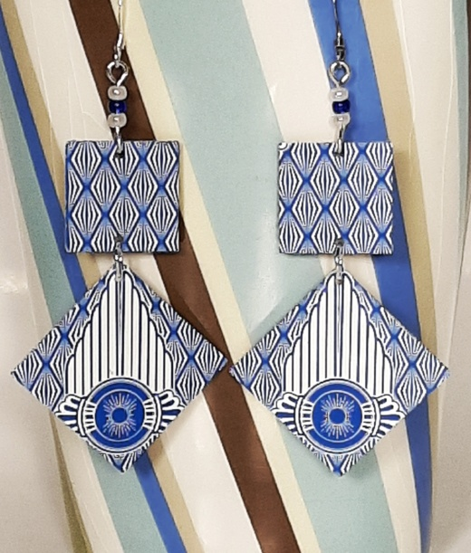 pair of blue and white dangling earrings, made of a square shape attached to a diamond.