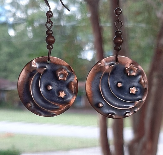 pair of large dangling copper earrings with imprint of moon and star.