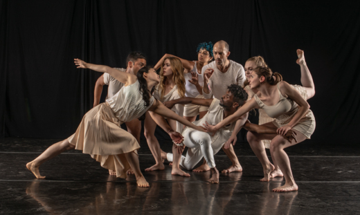 Photo of a group of diverse dancers wearing neutral colored clothing in a variety of simply styles, connected in a cluster.